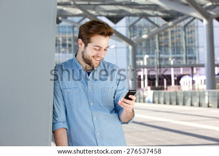Close up portrait of a smiling young man looking at mobile phone