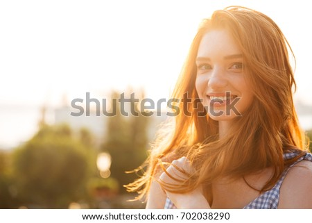 Close up portrait of a smiling young redhead girl with long hair looking at camera while standing outdoors with a city view