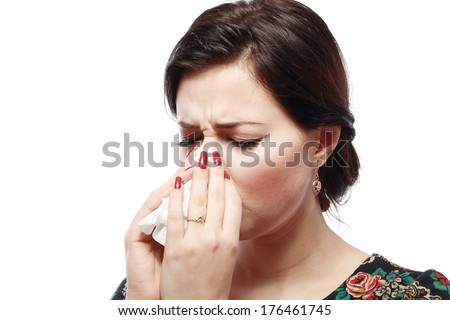 Close-up portrait of a sneezing woman with allergy or cold