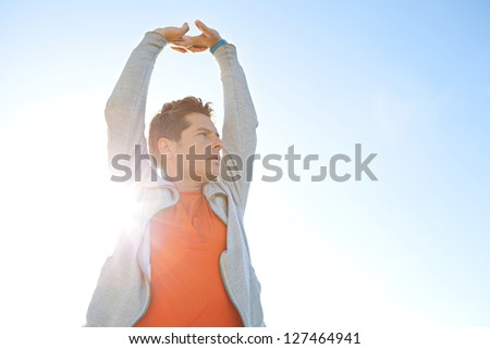 Close up portrait of a sports man stretching his arms up in the air against a sunny blue sky with sun rays filtering through his body.