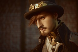 Close-up portrait of a stylish steampunk man in a coat and top hat on a brickwall background. Steampunk world.