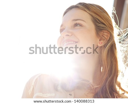 Close up portrait of a teenage girl in a city street during a sunny day, looking away from the camera and smiling against the sky with sun rays filtering through her neck.