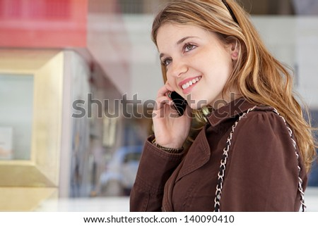 Close up portrait of a teenage girl in a shopping street, standing by a store glass window with reflections in the city, having a cell phone conversation and smiling holding her smartphone.