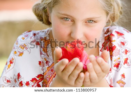 Close up portrait of a teenage girl smelling hibiscus flowers, smiling.