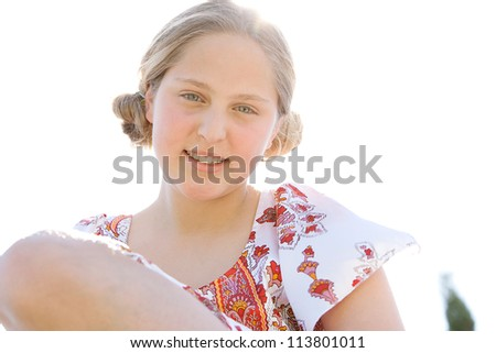 Close up portrait of a teenage girl smiling against a sunny sky.