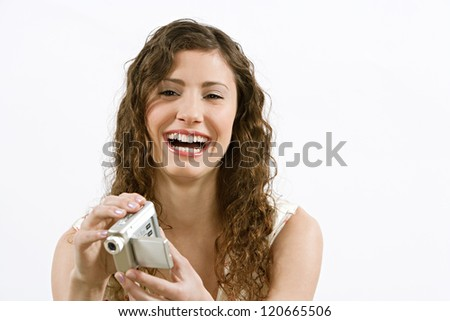 Close up portrait of a teenage girl using a small video camera to film while isolated against a white background, laughing and having fun.