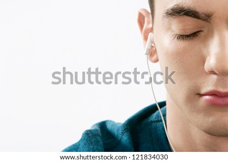 Close up portrait of a teenager's half face closing his eyes while listening to music with his headphones against a white background.