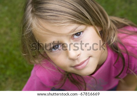 Close up portrait of a ten year old girl, smiling up at the camera. Positive emotion