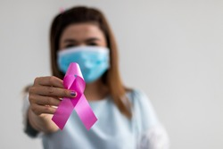 Close-up portrait of a Thai woman wearing a blue mask holding a pink bow, symbolic of the campaign against breast cancer.