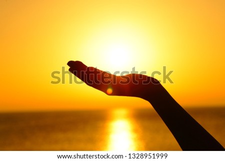Close up portrait of a woman hand silhouette holding sun at sunset on the beach