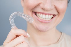 Close-up portrait of a woman holding a plastic transparent retainer. A girl corrects a bite with the help of an orthodontic device