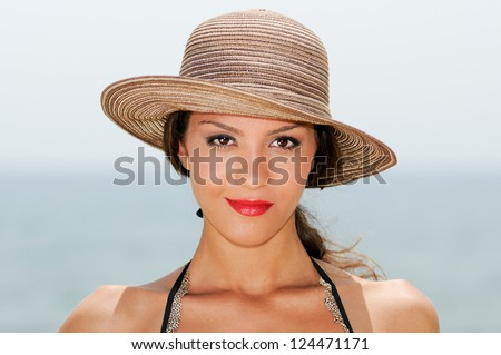 Close up portrait of a woman with a sun hat on a tropical beach