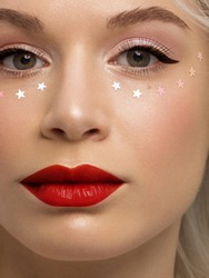 Close-up portrait of a woman with shiny clean skin and curly blond hair. Rhinestones stars on the eyes, evening makeup and red lipstick. soft care, full lips, long eyelashes and thick eyebrows