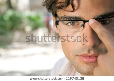 Close up portrait of a young and attractive businessman looking at the camera while holding his reading glasses with his finger.
