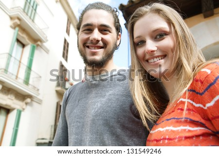 Close up portrait of a young and fun couple on vacation during a city break, visiting old architecture buildings and smiling with their heads together.