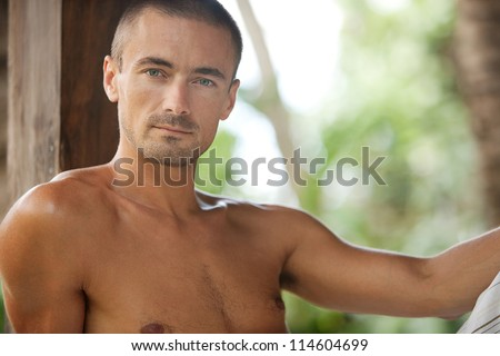 Close up portrait of a young attractive man relaxing on lounger while on vacation in a tropical destination.