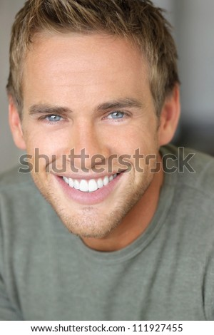 Close-up portrait of a young attractive man with great toothy smile