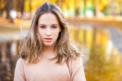 Close up portrait of a young beautiful blonde girl in beige sweater