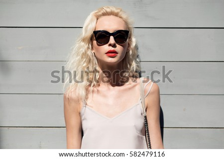 Close up portrait of a young beautiful blonde woman in light dress with clutch and sun glasses posing outside with wooden wall in background. Fashion accessories. Streetstyle summer spring photo #582479116