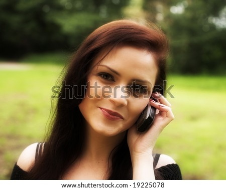 Close-up portrait of a young beautiful girl chatting by a cell-phone during her walk in a park