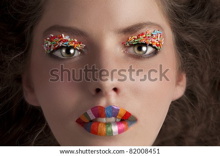 close up portrait of a young beautiful girl with rainbow lips and candy make up on her eyes