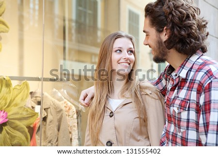 Close up portrait of a young bohemian couple looking at clothes in a store window while on vacations in a destination city, smiling.
