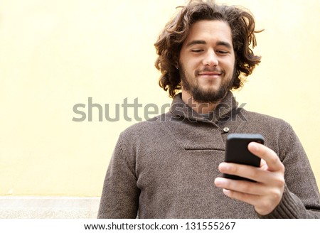 "Close up portrait of a young bohemian man using his ""smart phone"" while leaning on a yellow wall, smiling outdoors. - stock photo"