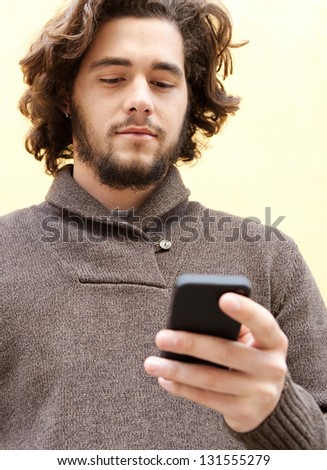 """Close up portrait of a young bohemian man using his """"smart phone"""" while leaning on a yellow wall, smiling outdoors."""