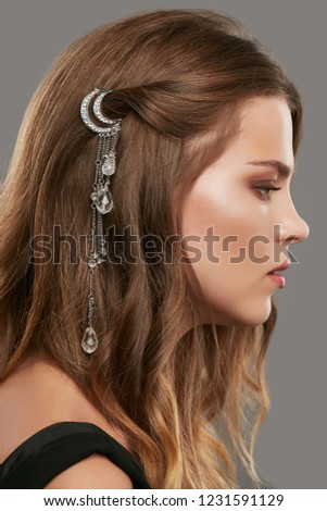 Close up portrait of a young brunette lady with natural make-up and wavy hairstyle. Her tresses are adorned with silver half moon hair clip. The side view of the girl posing over the grey background.