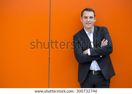 Close up portrait of a young business man in a dark suit and white shirt, against the backdrop of an orange wall #300732746