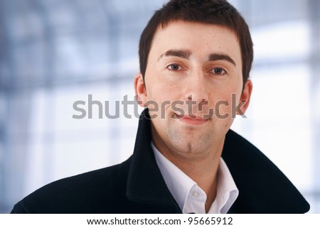 Close up portrait of a young businessman looking at you.