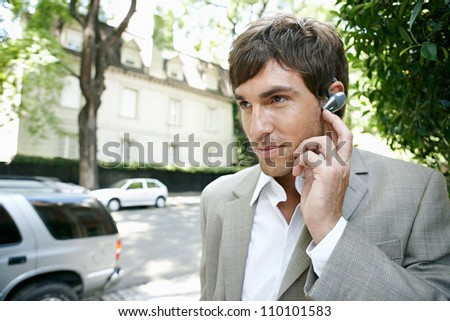 Close up portrait of a young businessman using an ear piece microphone to make a phone call.