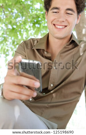 Close up portrait of a young businessman using his smart phone while sitting on a bench in a city park under green trees.