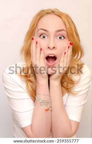Close up portrait of a young caucusian woman with curly blond hair scared, afraid and anxious. Screaming, with eyes wide open. Human emotions. Parody on a Munch Scream. Isolated on a white background.
