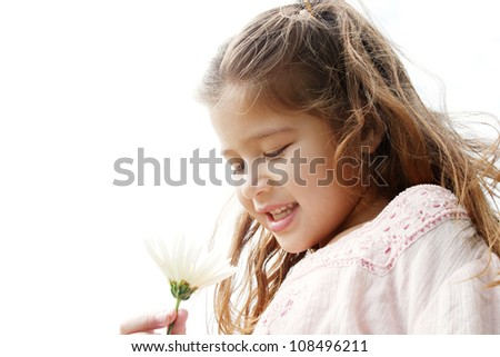 Close up portrait of a young girl holding a white daisy flower in her hand against the sky, smiling.