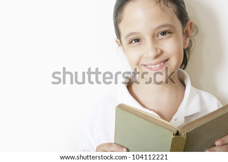 Close up portrait of a young girl reading a book against a white background.