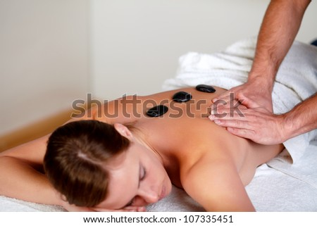 Close-up portrait of a young girl relaxing at a day spa, hot stone massage treatment