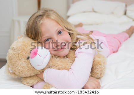 Close-up portrait of a young girl resting in bed with stuffed toy at home