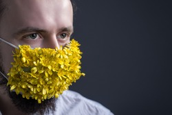 Close-up, portrait of a young guy, in a medical mask of flowers. Medical concept of coronavirus infection. Protection against colds by masking the airways. Spring concept of allergic