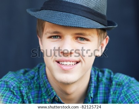 Close-up portrait of a young handsome man in a black hat .