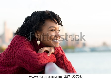 Close up portrait of a young happy african woman leaning on the banister of a bridge near river. Happy young african woman at river side thinking. Smiling pensive girl looking across river at sunset.