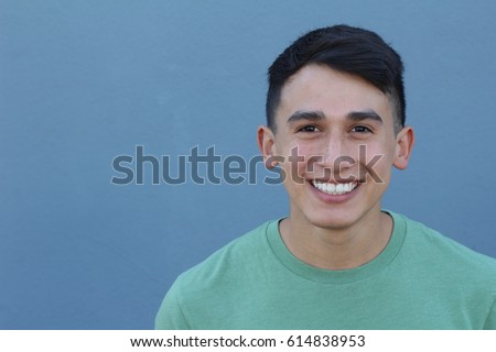Close up portrait of a young Hispanic teenager man looking at camera with a joyful smiling expression, against a blue background. Teenager being confident and smart. - Shutterstock ID 614838953