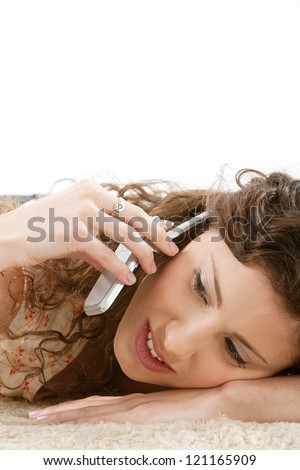 Close up portrait of a young hispanic woman laying down on a furry carpet at home, having a telephone conversation during a phone call.