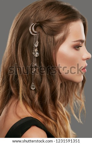 Close up portrait of a young lady with natural make-up and brown wavy hair. Her tresses are adorned with pink gold half moon hair clip. The side view of the girl posing against the grey background.
