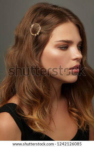 Close up portrait of a young lady with natural make-up and brown wavy hair. Her tresses are adorned with golden circle hair clip with star charms. Posing on the grey background, looking to the side.
