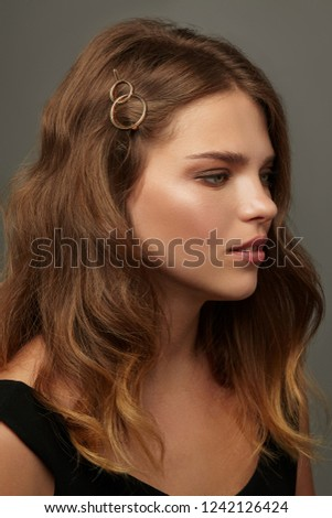 Close up portrait of a young lady with natural make-up and brown wavy hair. Her tresses are adorned with golden double circle hair clip. The girl posing over the grey background, looking to the side.