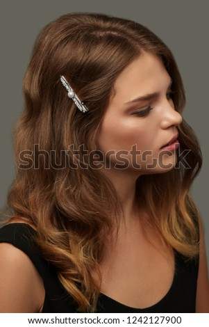 Close up portrait of a young lady with natural make-up and brown wavy hair. Her tresses are adorned with pearl-studded silver barrette. The girl posing over the grey background, looking to the side.