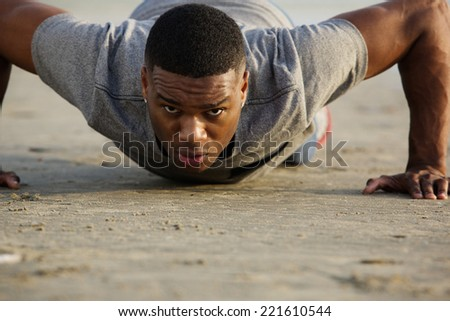 Close up portrait of a young man doing push ups outdoors