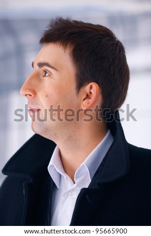 Close up portrait of a young man in coat, side view.