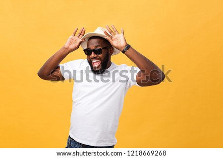 baeee990df3 Close up portrait of a young man laughing with hands holding hat isolate  over yellow background